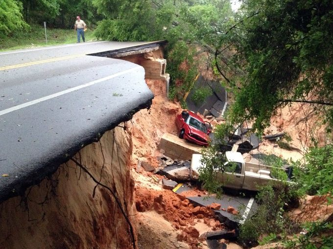 A piece of roadway has collapsed in Pensacola, Florida due to flooding. Photo credit Pensacola News Journal